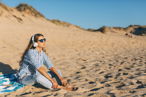 Portugal, Aveiro, woman sitting near beach dune listening music with headphones - JPF00276