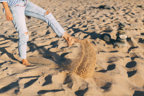 Woman standing on one leg throwing sand on the beach, partial view - JPF00279