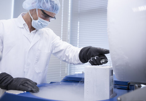Scientist in lab storing biological material in cryo store - WESTF23632