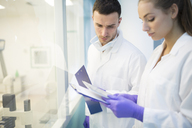 Man and woman in lab coats with clipboards - WESTF23641