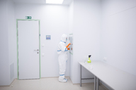 Lab technician wearing cleanroom overall at material sluice - WESTF23659