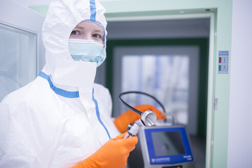 Lab technician wearing cleanroom overall holding apparatus at material sluice - WESTF23662