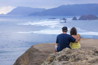 Indonesia, Lombok, couple sitting at the coast looking at view - KNTF00901