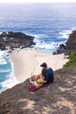 Indonesia, Lombok, couple sitting at the coast looking at view - KNTF00904