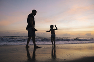 Indonesia, Bali, father and son on the beach at sunset - KNTF00916