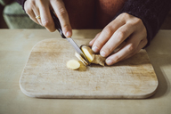 Woman's hands cutting ginger on wooden board, close-up - JSCF00011