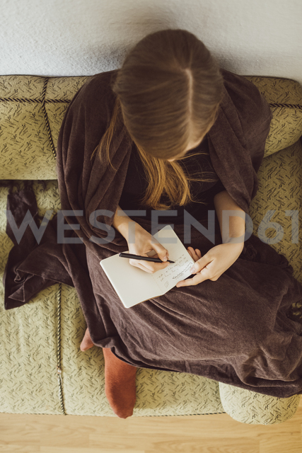 Woman sitting on couch in the living room writing in notebook, top view - JSCF00017
