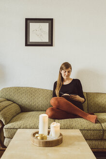 Woman sitting on couch in the living room writing in notebook - JSCF00020