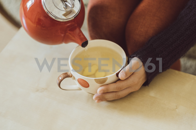 Woman pouring water into tea cup with chopped fresh ginger, close-up - JSCF00023 - Jonathan Schöps/Westend61