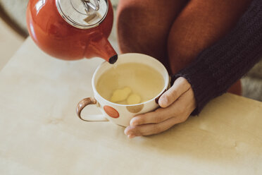 Woman pouring water into tea cup with chopped fresh ginger, close-up - JSCF00023