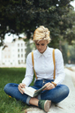 Teenage girl sitting cross-legged in a park, reading book - GIOF03311
