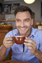 Portrait of laughing man with cup of coffee in a coffee shop - PNEF00342