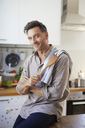 Portrait of smiling man with cooking spoon in the kitchen - PNEF00348