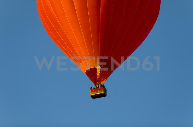 Red air balloon against blue sky, partial view - KLR00544