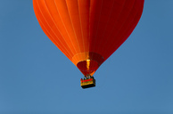 Red air balloon against blue sky, partial view - KLR00544