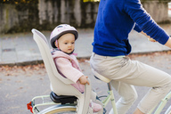 Mother and daughter riding bicycle, baby wearing helmet sitting in children's seat - DIGF03168