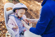 Mother and daughter riding bicycle, baby wearing helmet sitting in children's seat - DIGF03171