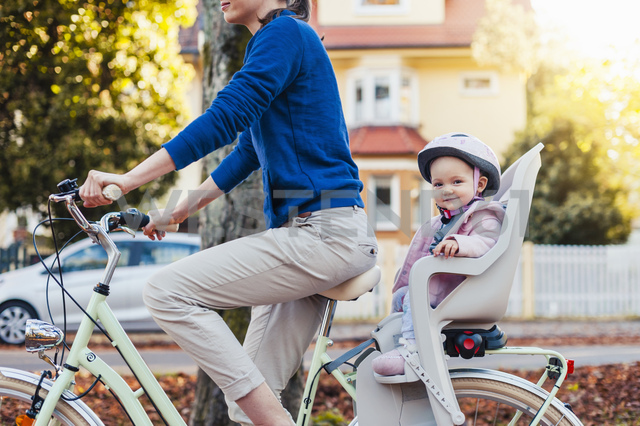 Mother and daughter riding bicycle, baby wearing helmet sitting in children's seat - DIGF03174