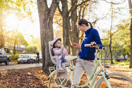 Mother and daughter riding bicycle, baby wearing helmet sitting in children's seat - DIGF03177