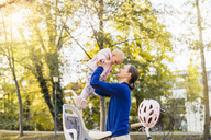 Mother and daughter riding bicycle, lifting baby  from children's seat - DIGF03180