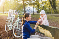 Mother and daughter taking a break on a park bench - DIGF03183