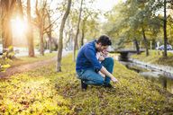 Father searching for chestnuts in park, with baby daughter on his lap - DIGF03186