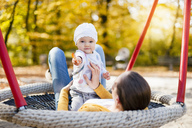Portrait of baby girl relaxing with her mother on a swing in autumn - DIGF03190