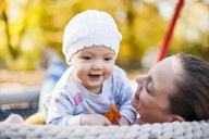Portrait of happy baby girl relaxing with her mother on a swing in autumn - DIGF03193