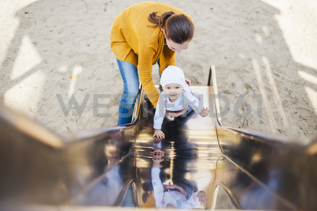 Smiling baby girl on shute on playground being held by her mother - DIGF03196 - Daniel Ingold/Westend61