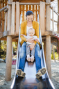 Happy baby girl sitting with her mother on shute on playground - DIGF03199