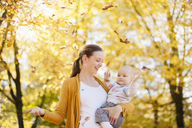 Mother and baby girl having fun with leaves in autumn - DIGF03205