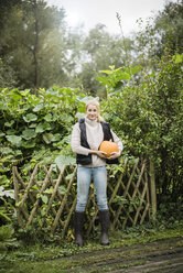 Portrait of smiling young woman holding pumpkin in garden - JOSF01881