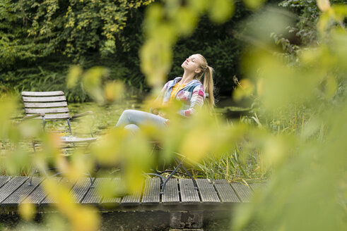 Young woman relaxing on jetty in garden - JOSF01890
