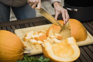 Woman cutting pumpkin on garden table - JOSF01896