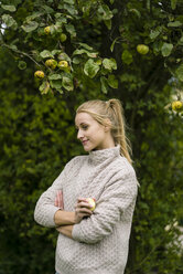 Smiling young woman at apple tree in garden - JOSF01899
