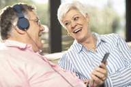 Happy senior couple with cell phone and headphones on couch at home - ZEF14730