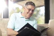 Smiling senior man sitting on couch looking at photo album - ZEF14736