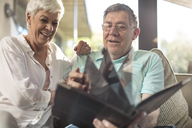 Happy senior couple sitting on couch looking at photo album - ZEF14739