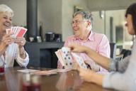 Senior couple playing cards with daughter at home - ZEF14763