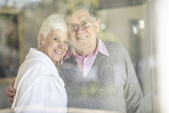 Portrait of smiling senior couple behind windowpane - ZEF14766