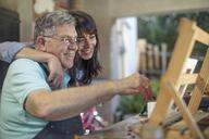 Smiling woman embracing senior man painting - ZEF14772
