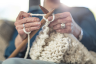 Senior woman knitting on couch at home - ZEF14775