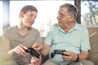 Grandfather and grandson playing video game on couch at home - ZEF14778