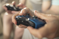 Close-up of hand holding video game controller - ZEF14781