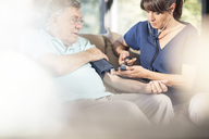 Nurse taking blood pressure of senior patient at home - ZEF14784
