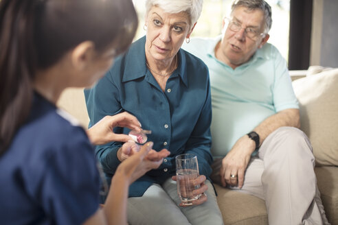 Nurse giving medication to senior woman at home - ZEF14790