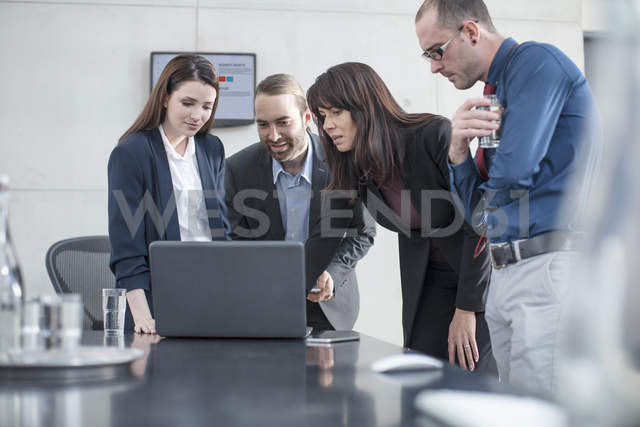 Colleagues having a meeting with laptop in conference room - ZEF14808