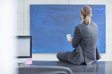Businessman in office sitting on desk looking at a blue painting - ZEF14820