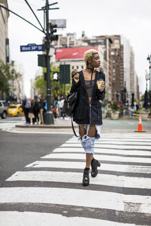 USA, New York City, fashionable young woman with coffee to go crossing the street - MAUF01218