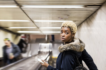 Portrait of young woman with cell phone on escaltor in underground station - MAUF01227